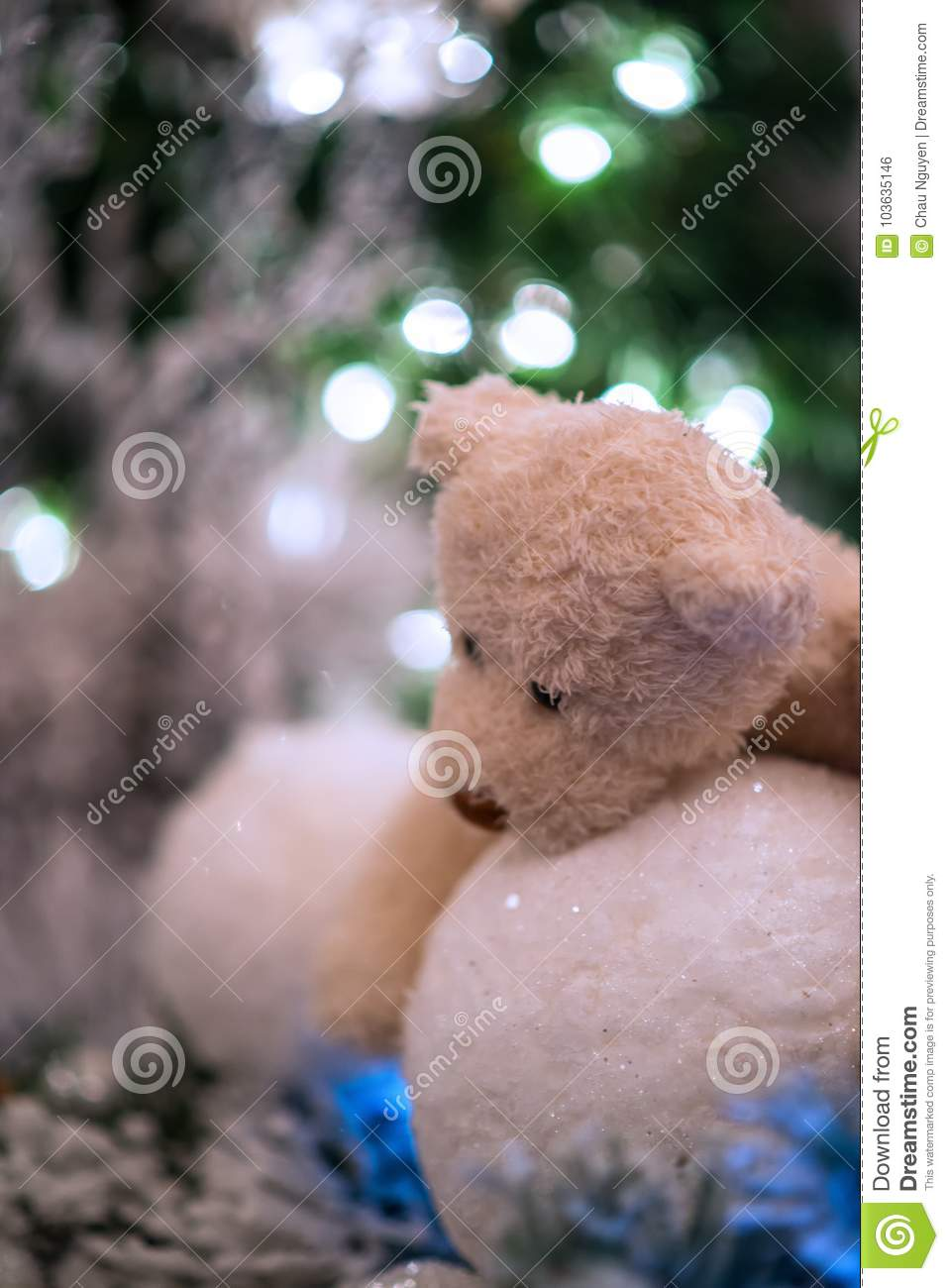Teddy bear hugs white snowballs with christmas lights brighten up in the background.