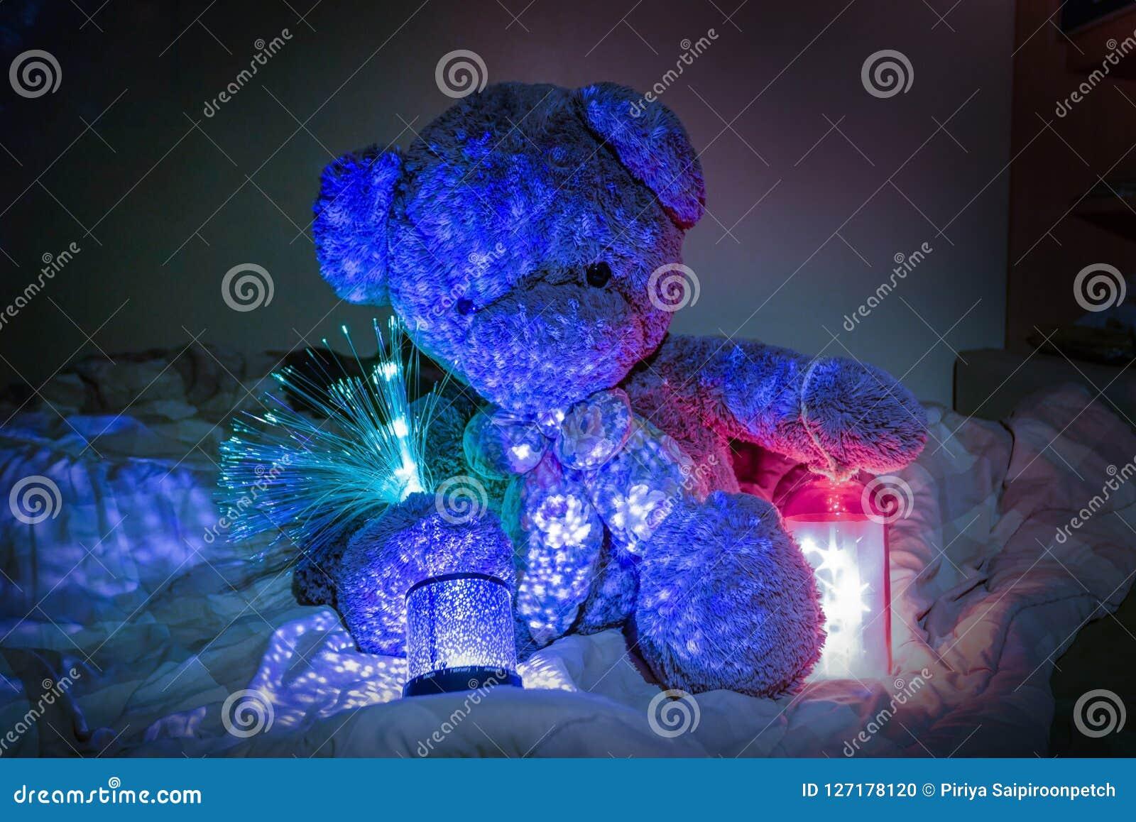 Teddy Bear mit dekorativen Lichtern und Stern beleuchtet im Bett Stockfoto