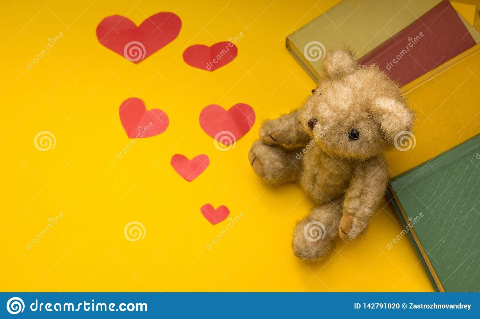 A teddy bear sits near books on a yellow background of scattered hearts