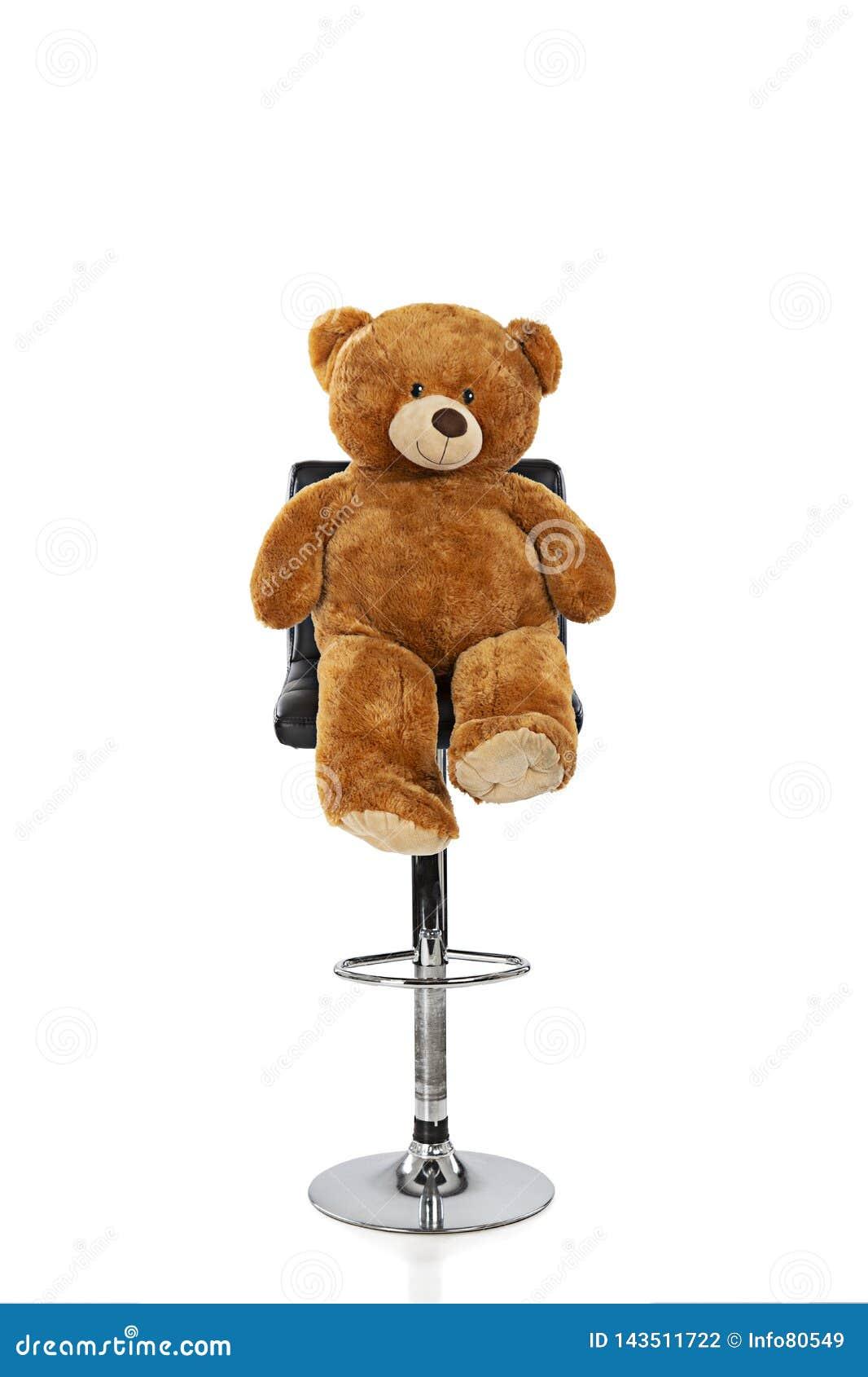 Teddybär, der auf einem Schemel mit einem weißen Hintergrund sitzt
