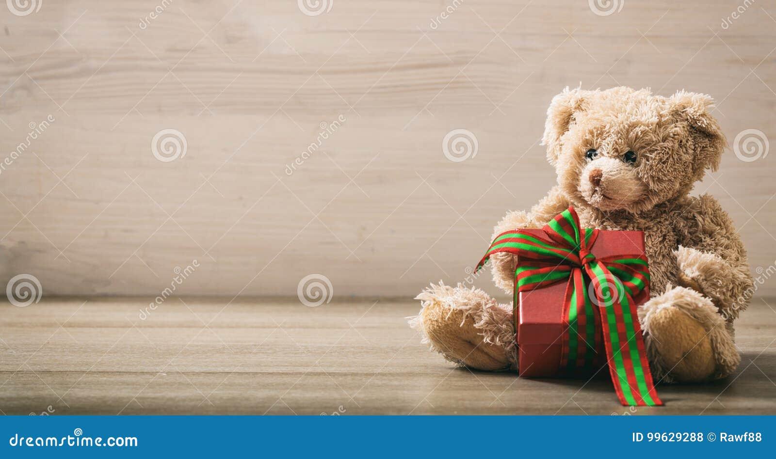 Teddybär holdimg ein Geschenk auf einem Bretterboden