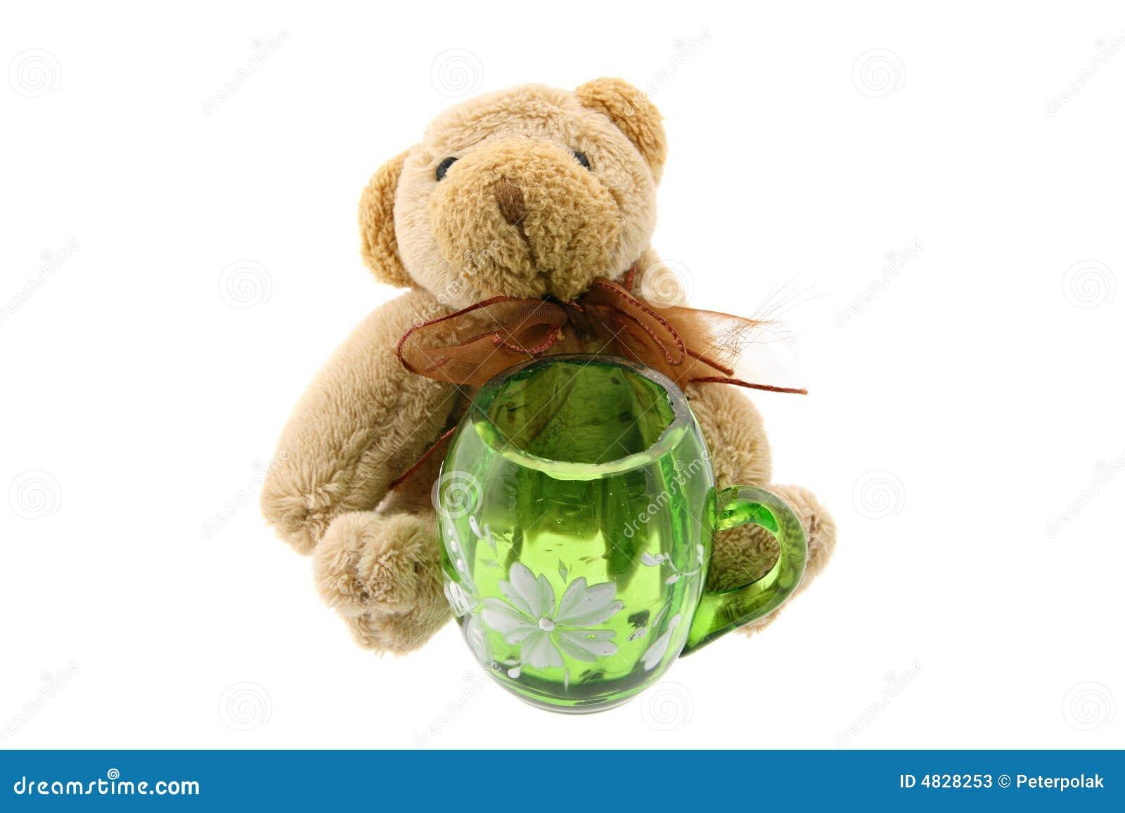 Teddybär mit einem grünen Krug getrennt auf Weiß