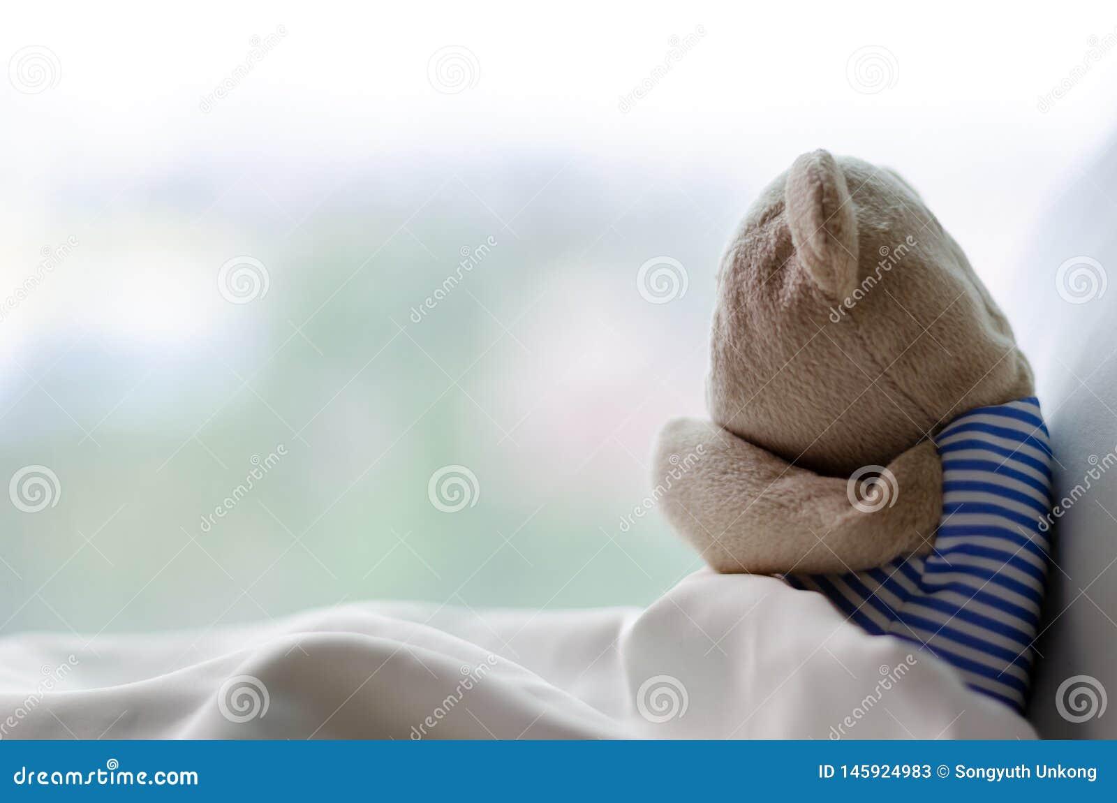 Teddybeer die op bed in de droevig dag snikken