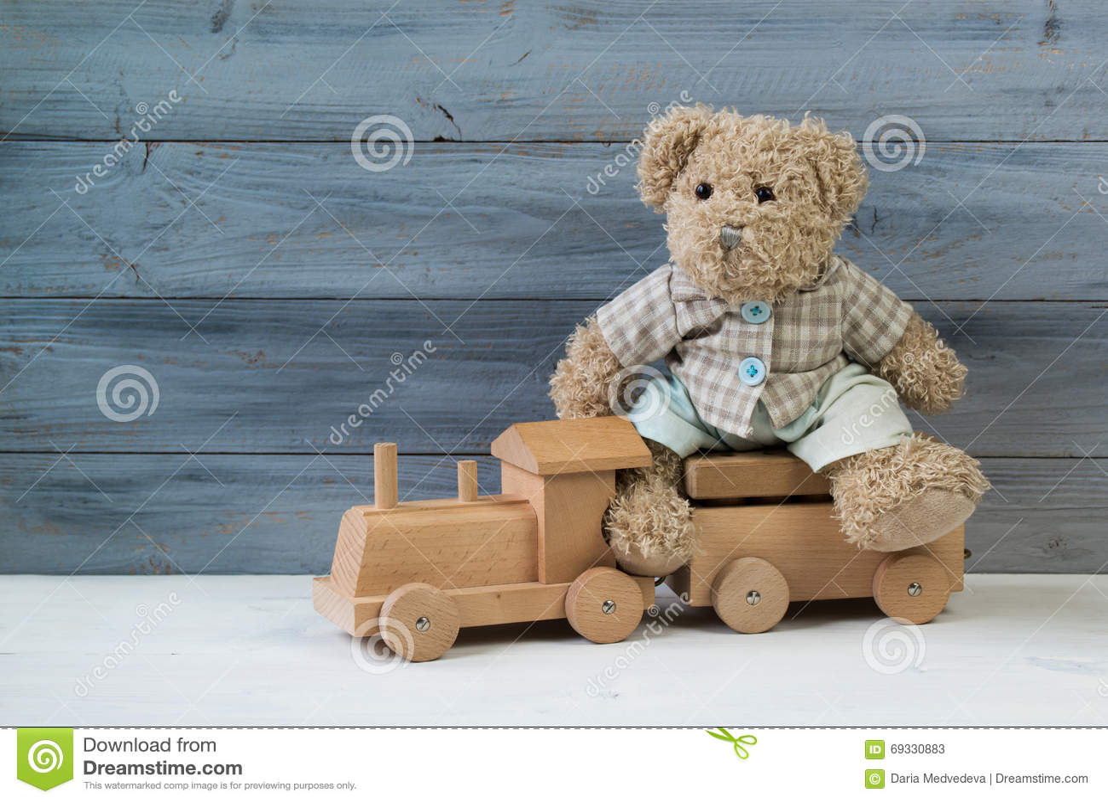 Teddybeerzitting op de stuk speelgoed houten trein, houten achtergrond