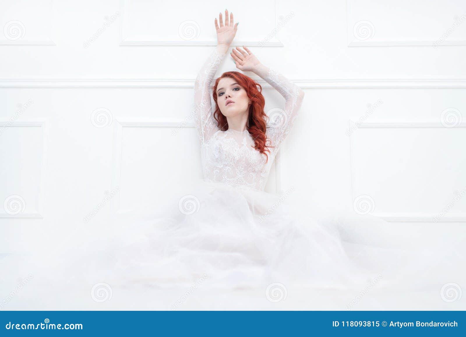 Teder retro portret van een jonge mooie dromerige roodharigevrouw in mooie witte kleding