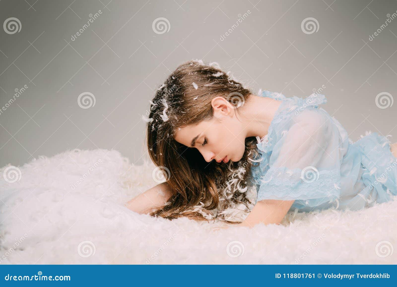 Tederheid en breekbaarheid van de jeugdconcept Zijaanzichttiener die op slaperig bed op grijze achtergrond liggen Mooi