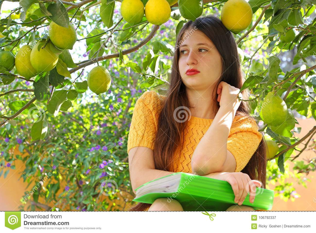 A teen age girl is learning in the garden under a lemon tree