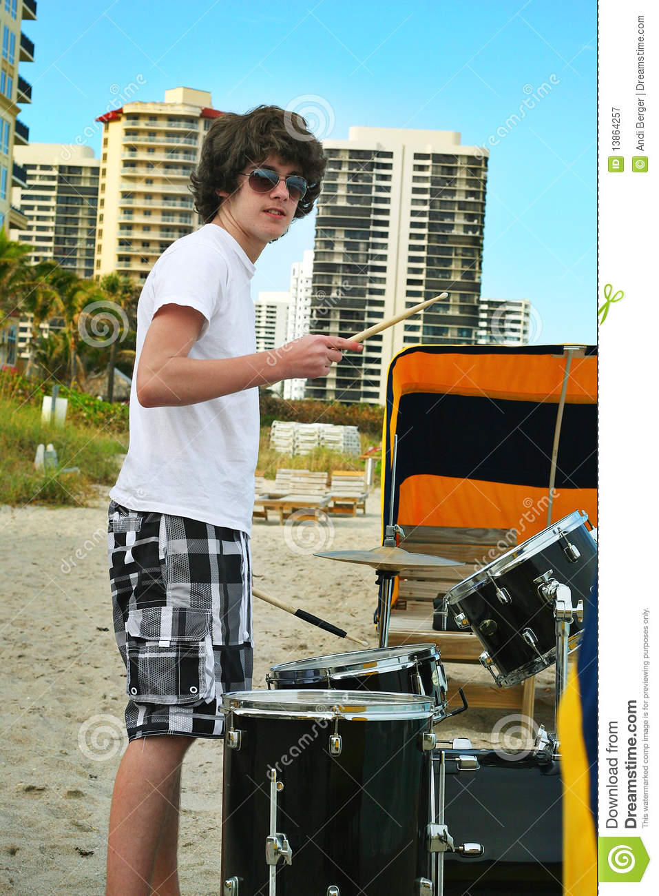 Teen boy with drums on the beach