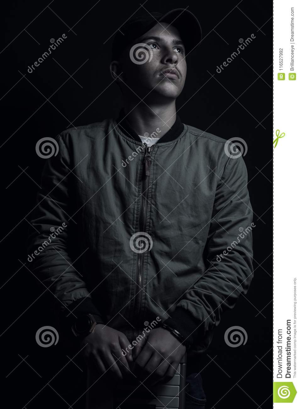 Teen boy posing looking up with black cap and bomber jacket in front of black background