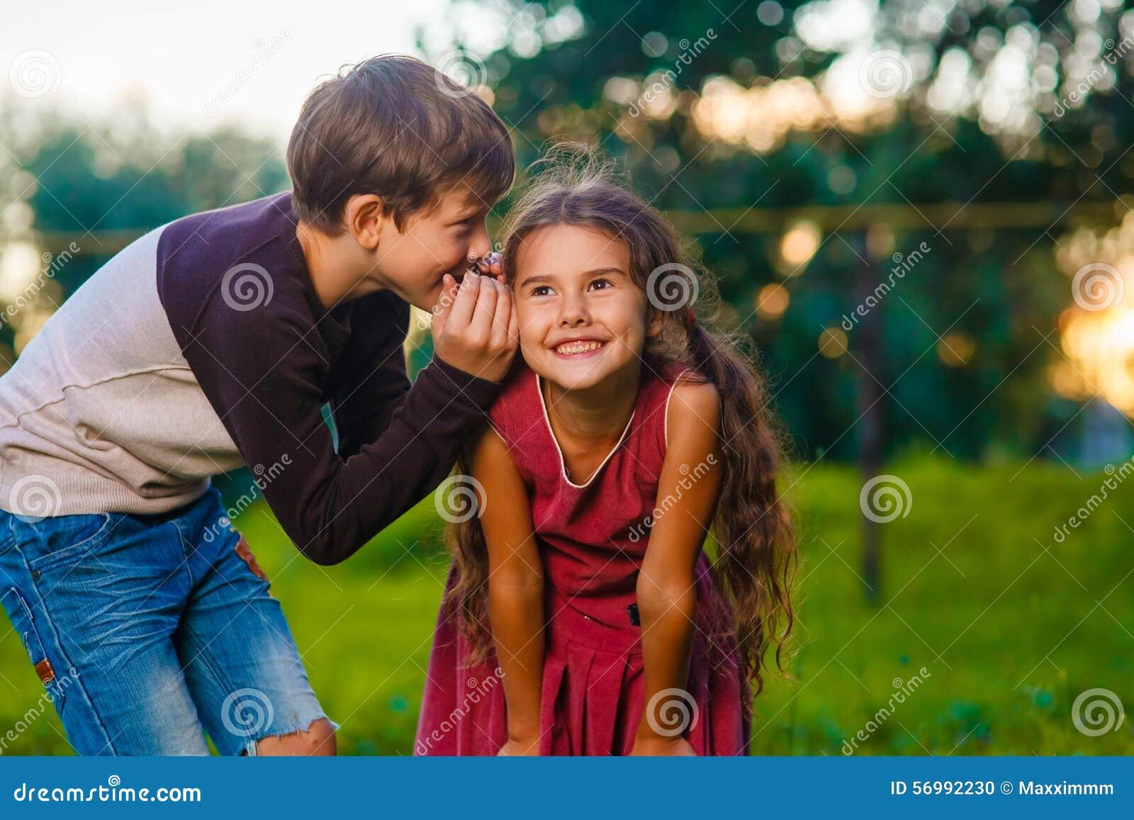 Teen boy whispering secret gossip girl child s ear