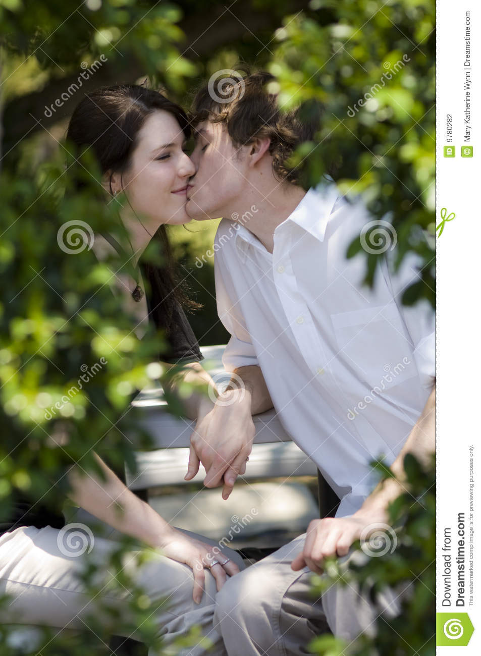 Teen couple kissing in park