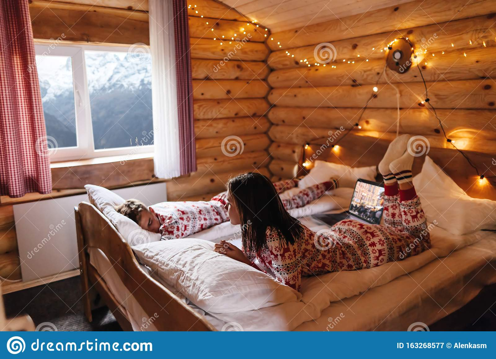 Teen Friends In Same Christmas Pajamas Relaxing In Bed ...