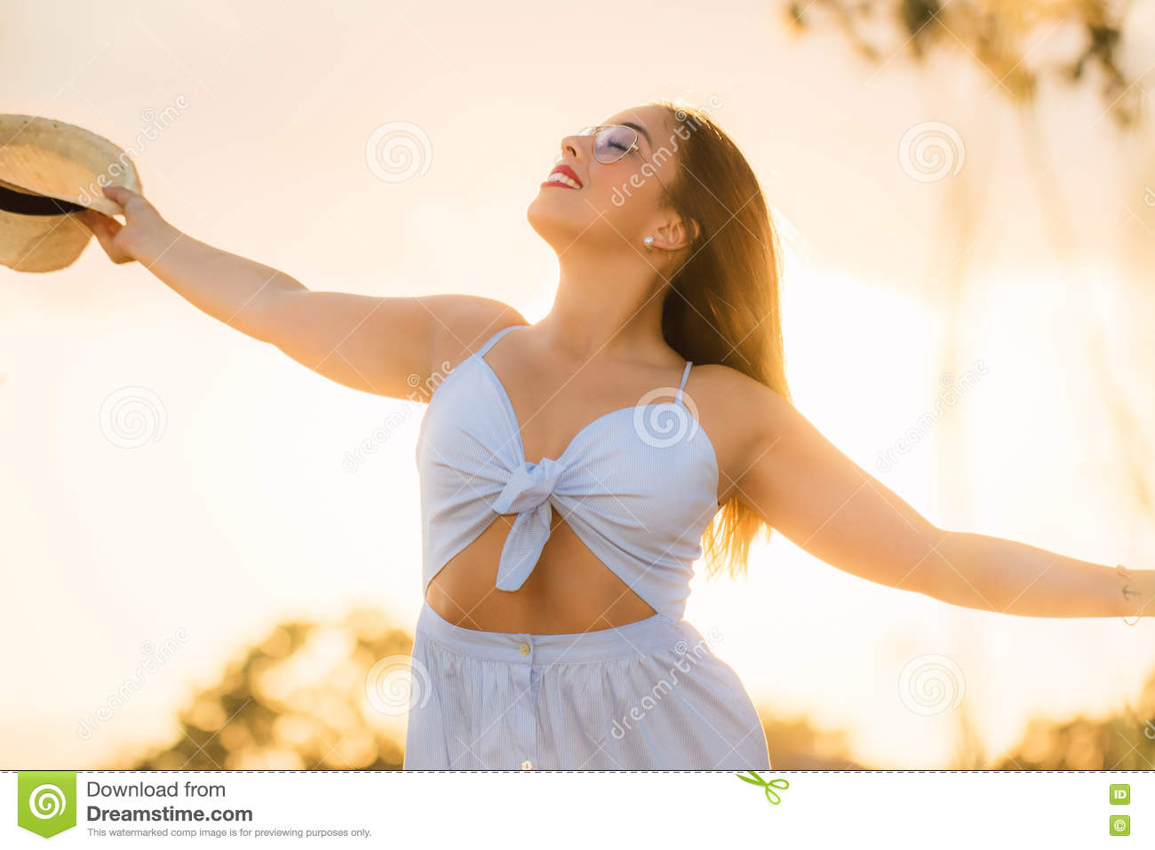 Teen girl with arms open at sunset.