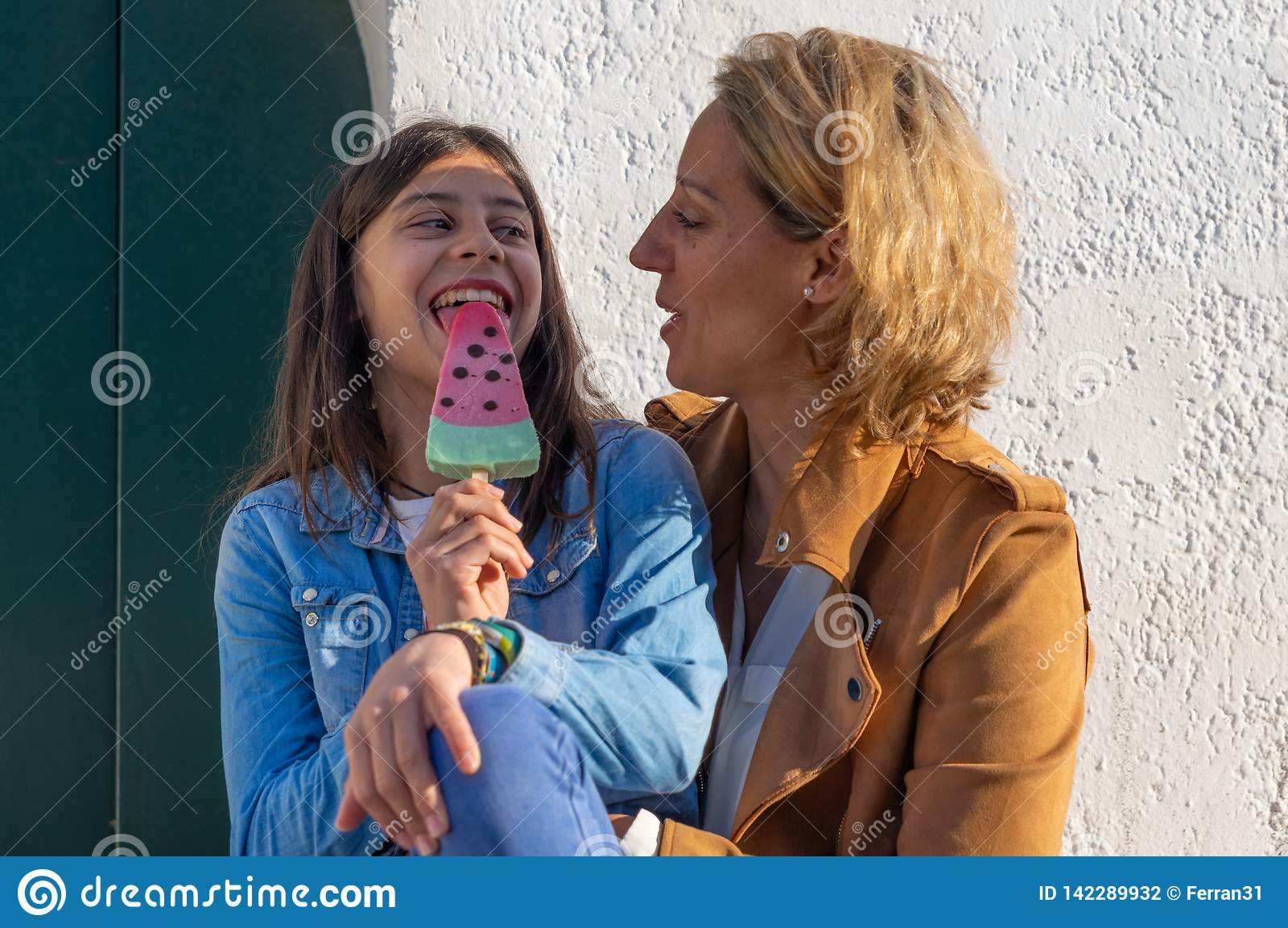 Teen girl eating a watermelon ice cream next to her mother in coastal town of Europe