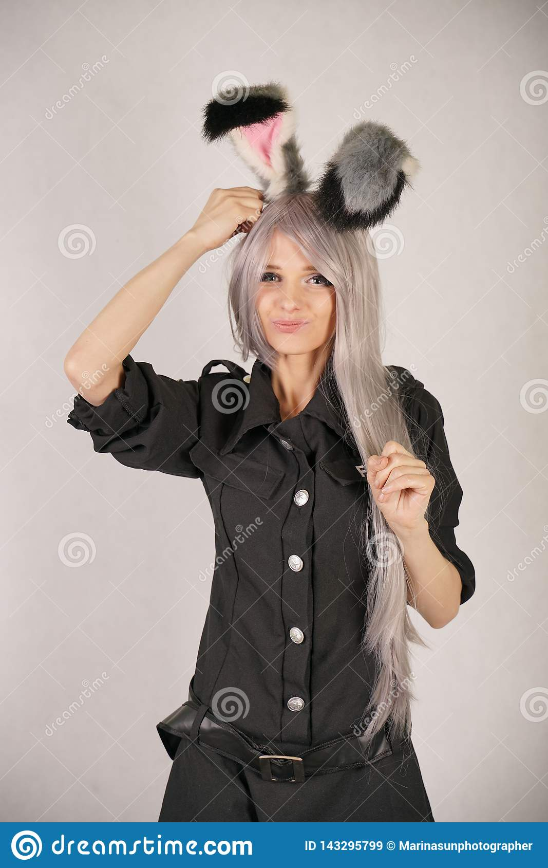 Teen girl in FBI black carnival dress with big fur rabbit ears loves cosplay and stands on white Studio background