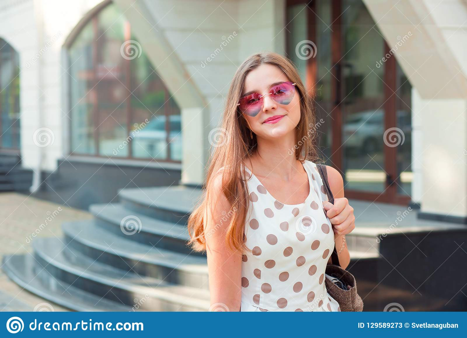Girl with long brunette hair in pink heart-shaped sunglasses smiling outdoors