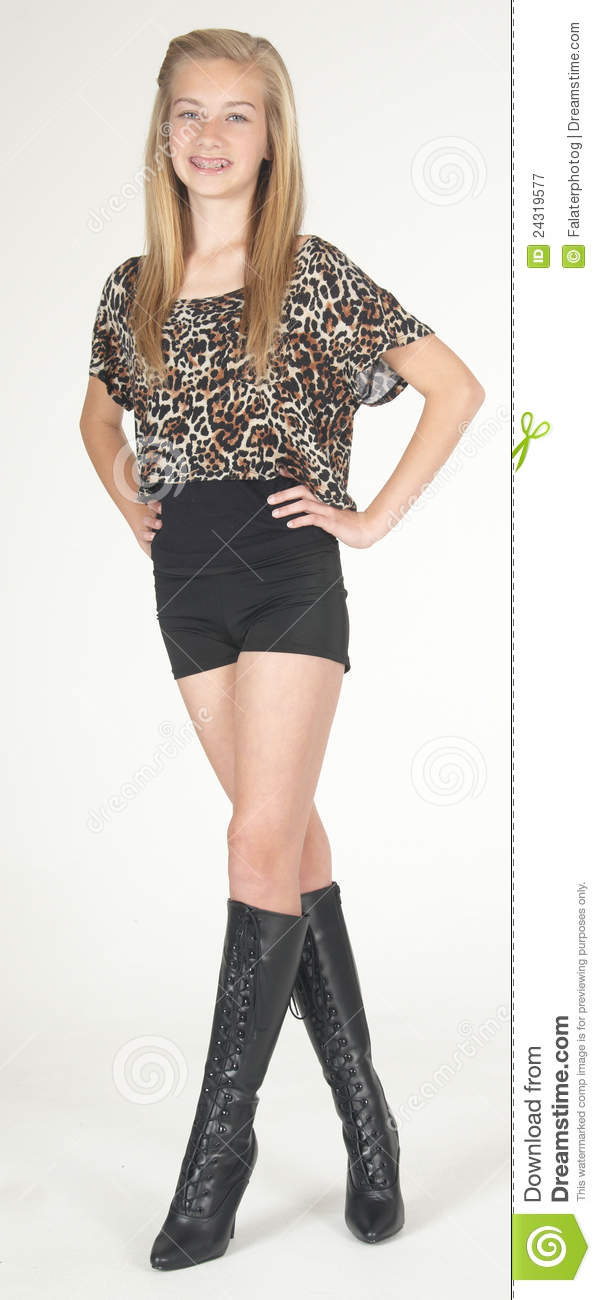 Teen girl modeling boots, shorts and colorful top in studio against a ...