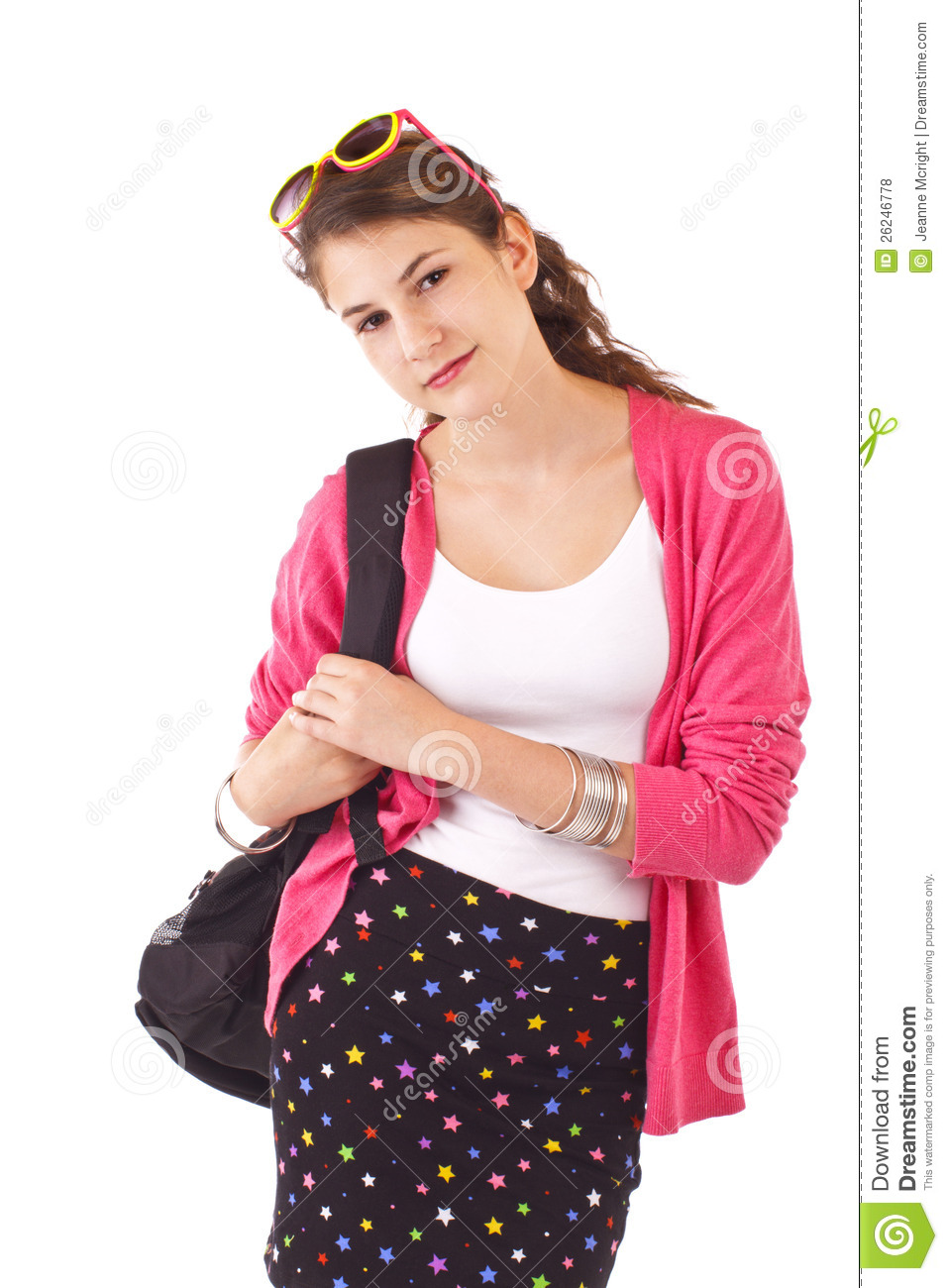 Pretty smiling teenage girl in fashionable back to school clothes carries a  backpack over her shoulder. Pink sweater, sunglasses on top of head,