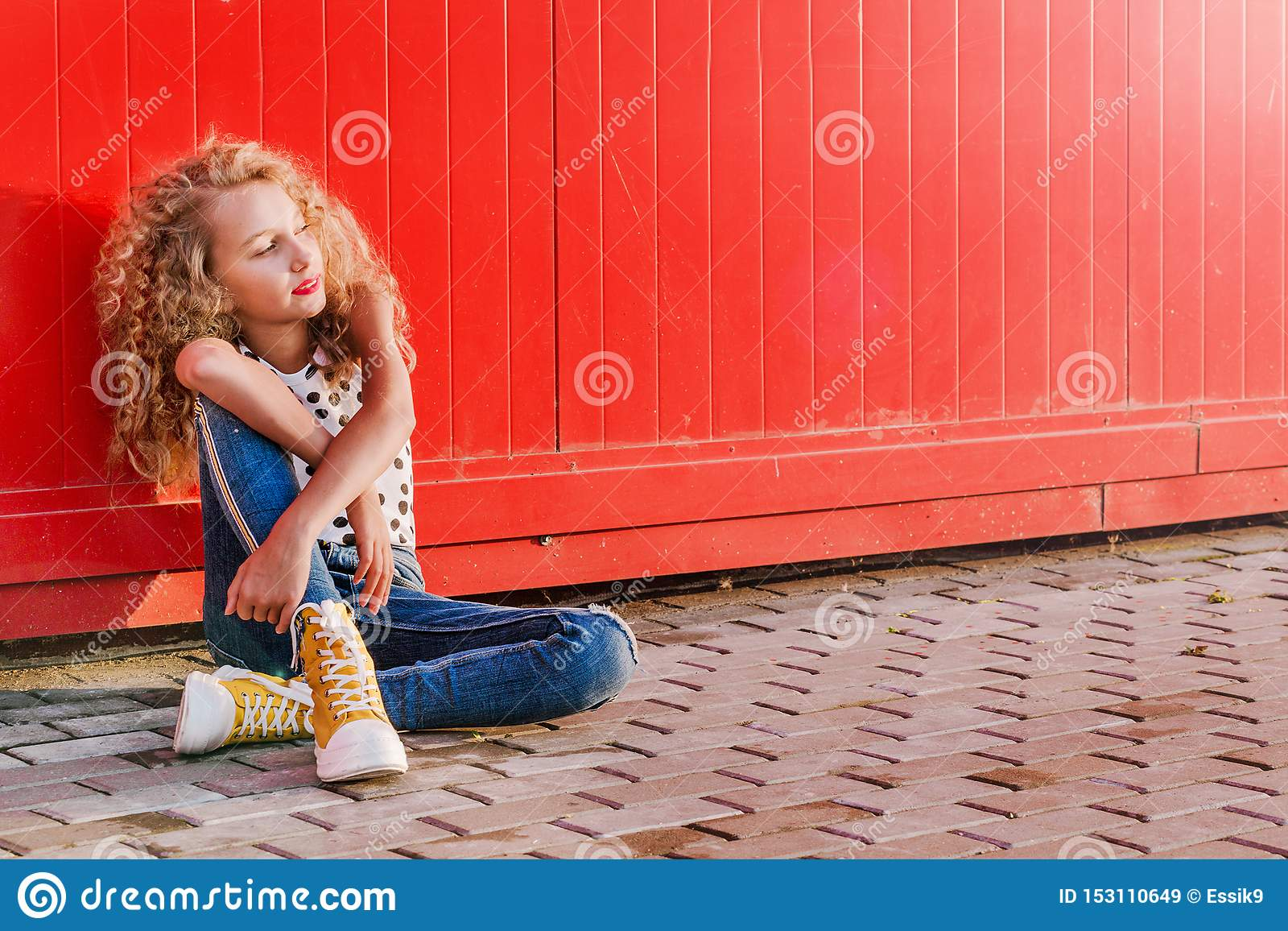Teen girl sits against a red wall on a city street