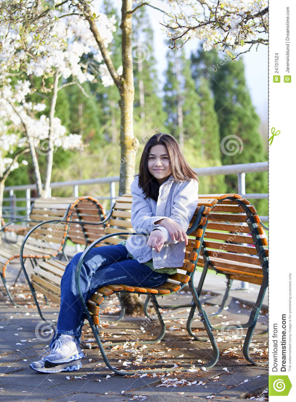 Teen Girl Sitting On Bench Under Cherry Tree Stock Photo