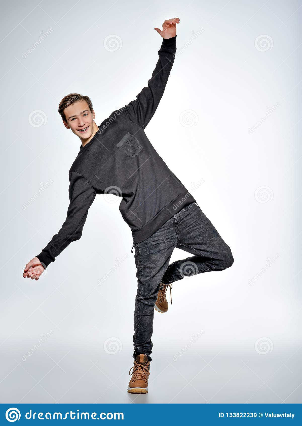 Teen pojkedans Iklädd svart moderiktig kläder för tonåring