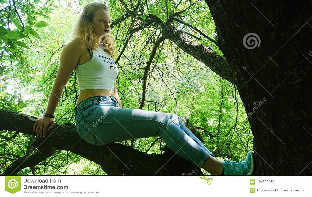 Teen posing on a large tree branch on a sunny day