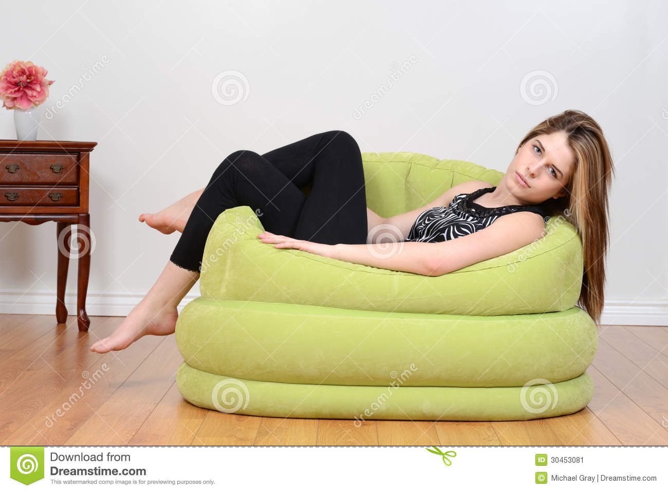 Teen Relaxing In Green Bean Bag Chair