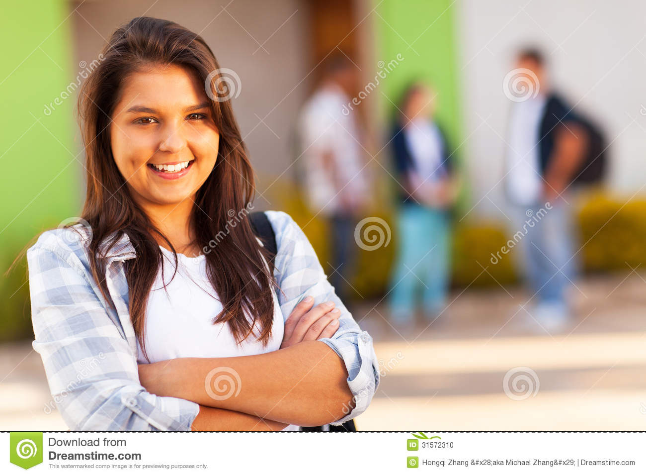 Portrait of cute teen high school girl with arms folded.
