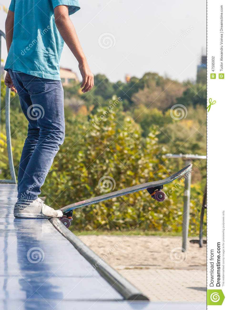 Teen with skateboard ready for a stunt on a half pipe ramp.