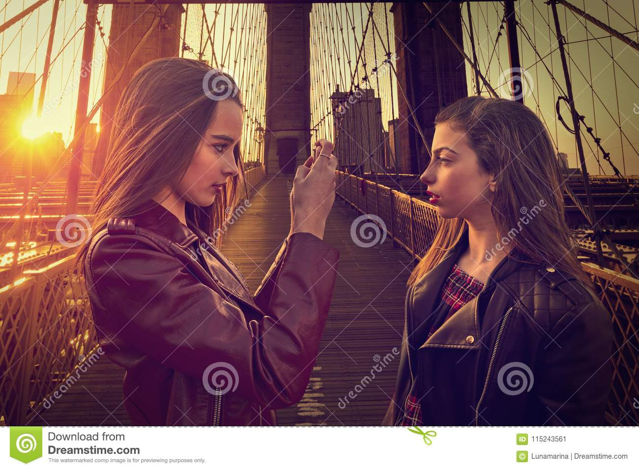 Teen tourist girls taking photo in Brooklyn bridge NY