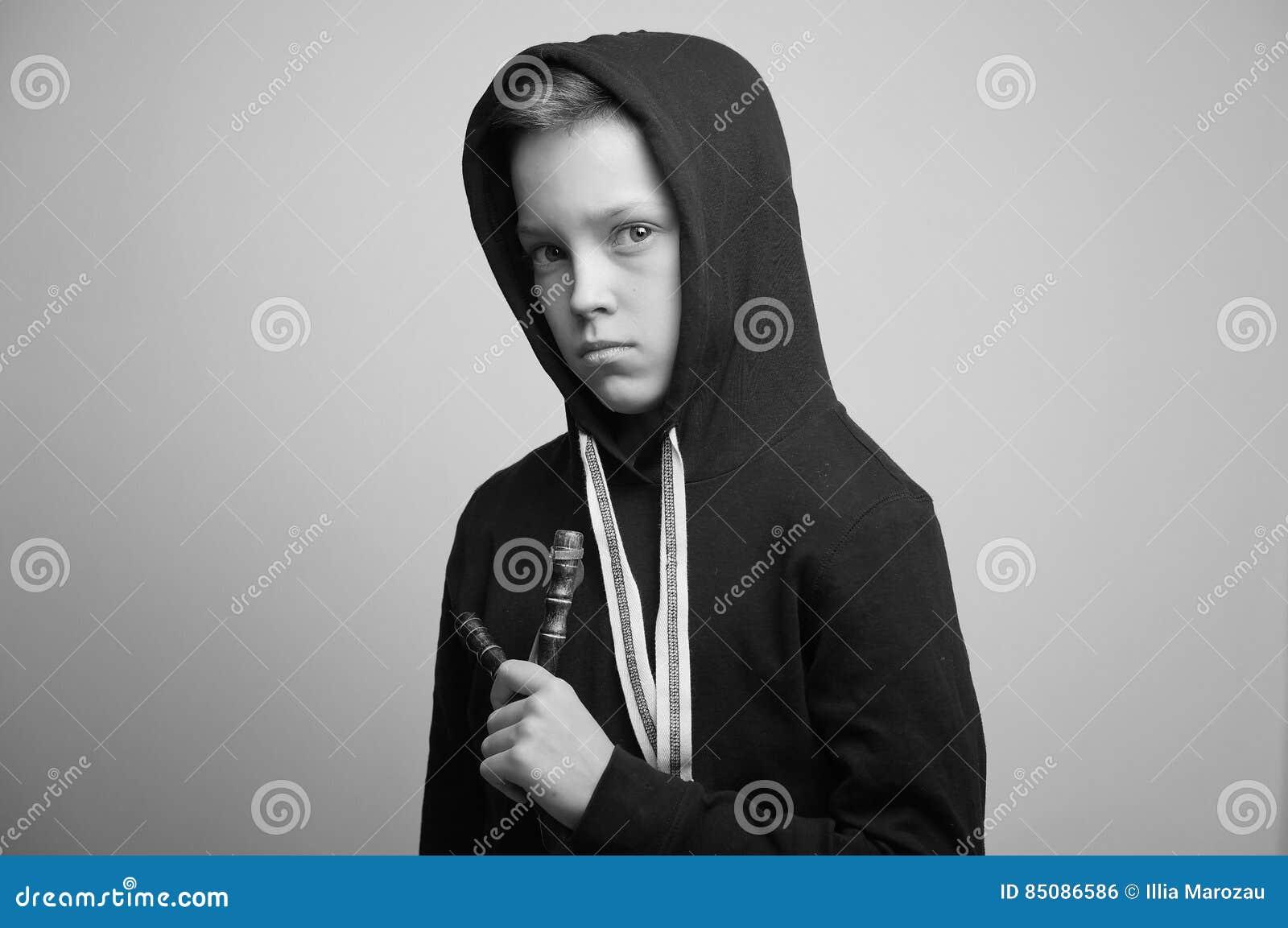 teenage bad boy with slingshot and stylish haircut studio shot