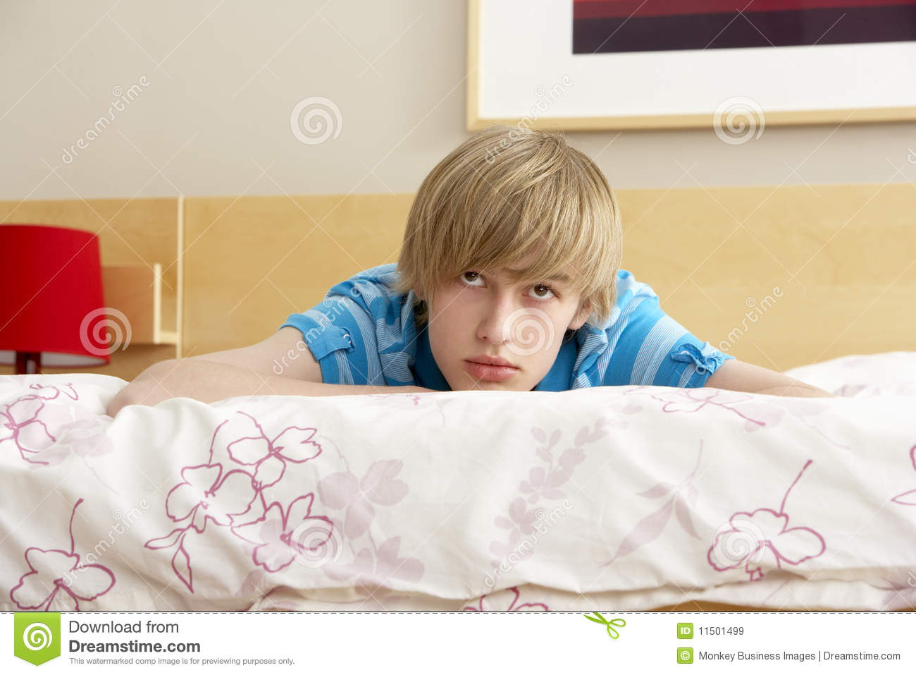 Teenage Boy In Bedroom Looking Sad