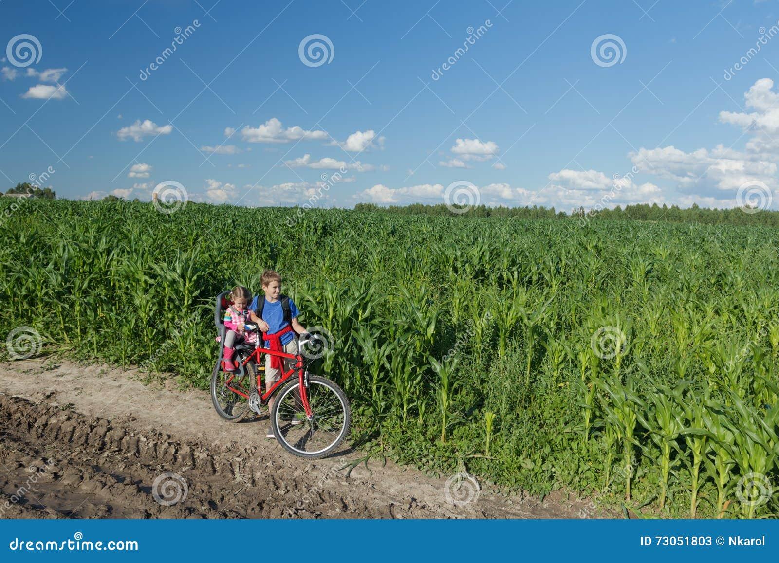 Teenage boy carrying his little sibling sister on baby bike seat on farm corn field summer dirt road