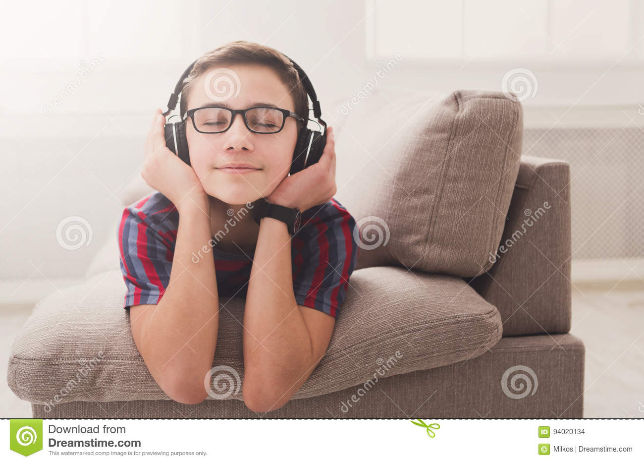 Teenage boy enjoying music in headphones at home
