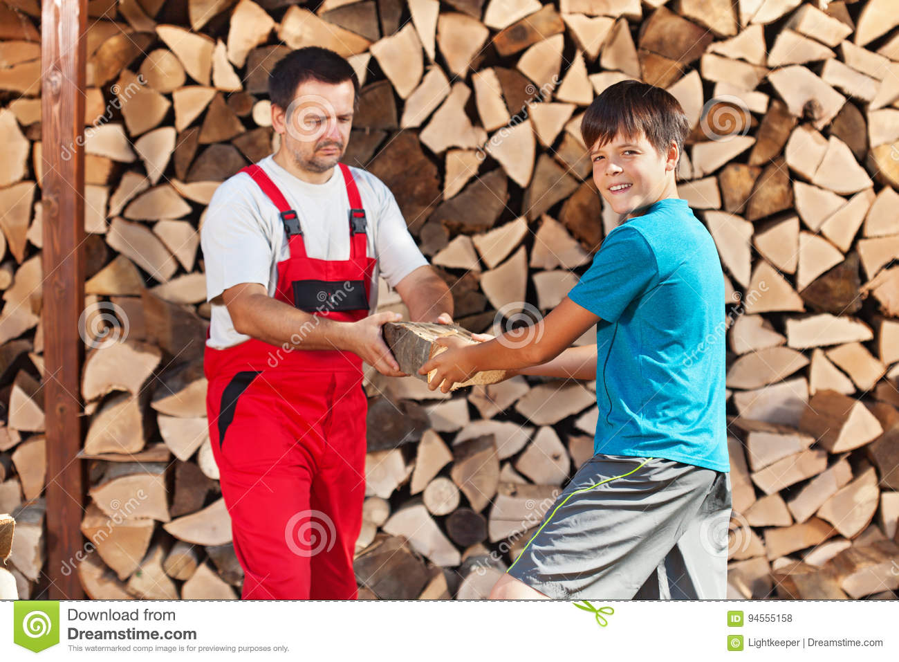 Teenage boy helping father stack the firewood
