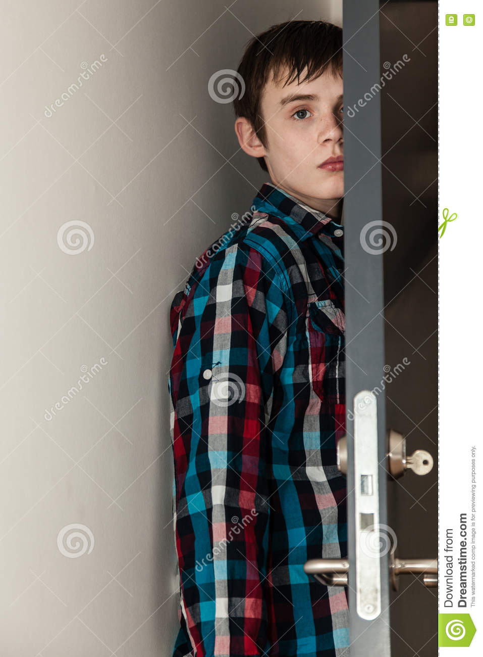 Teenage Boy Hiding Behind Open Door In Home Stock Photo