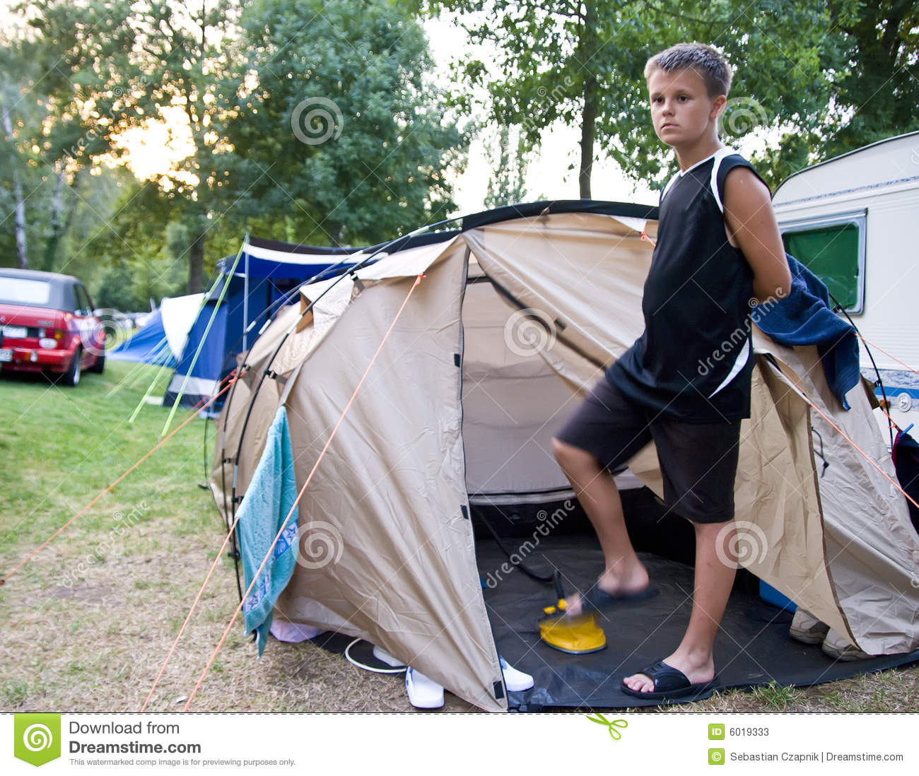 ... teenage boy inflating a mattress with a foot pump, standing at a tent