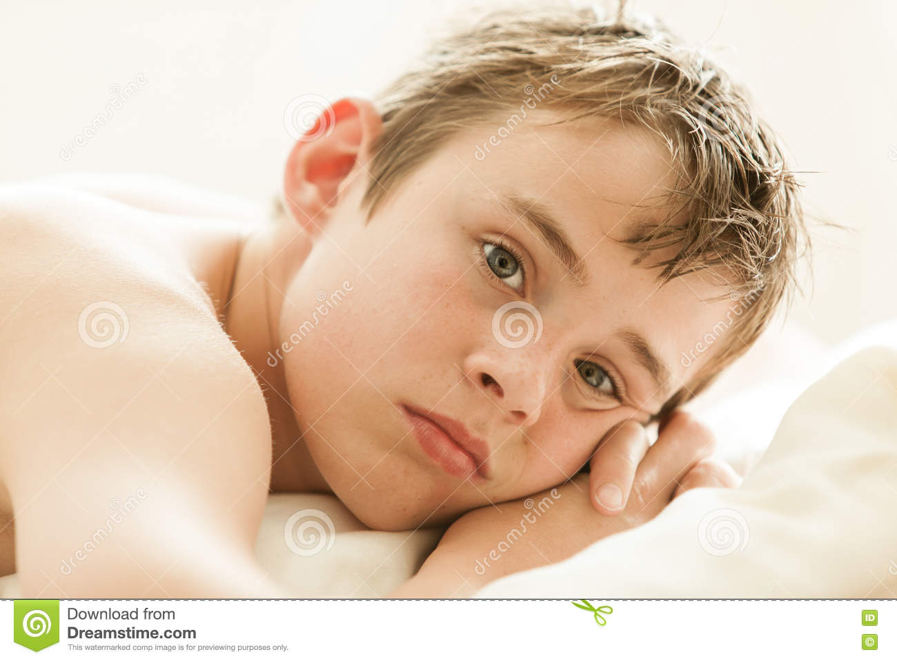 Teenage Boy Lying On Bed With Head On Hands Stock Photo ...