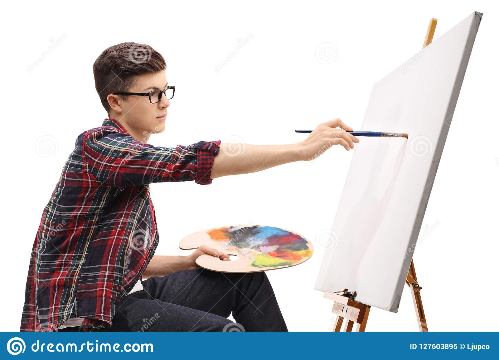Teenage boy painting on a canvas