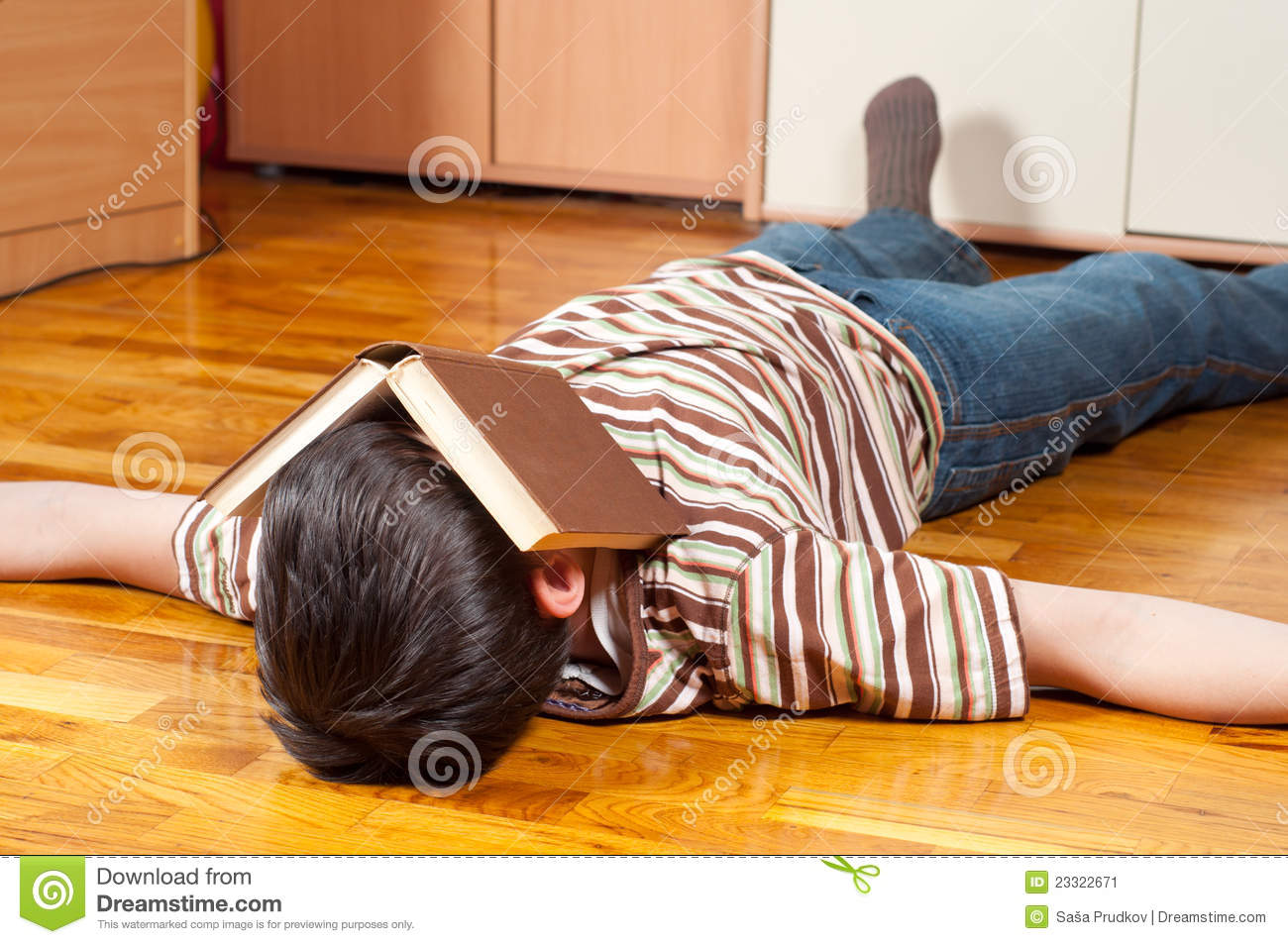 Book Covering Face : Teenage boy sleeping with book covering his face stock