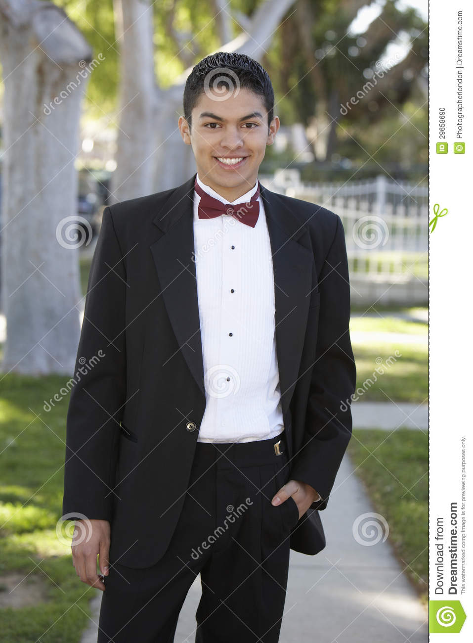 teenage boy in tuxedo standing with hand in pocket at