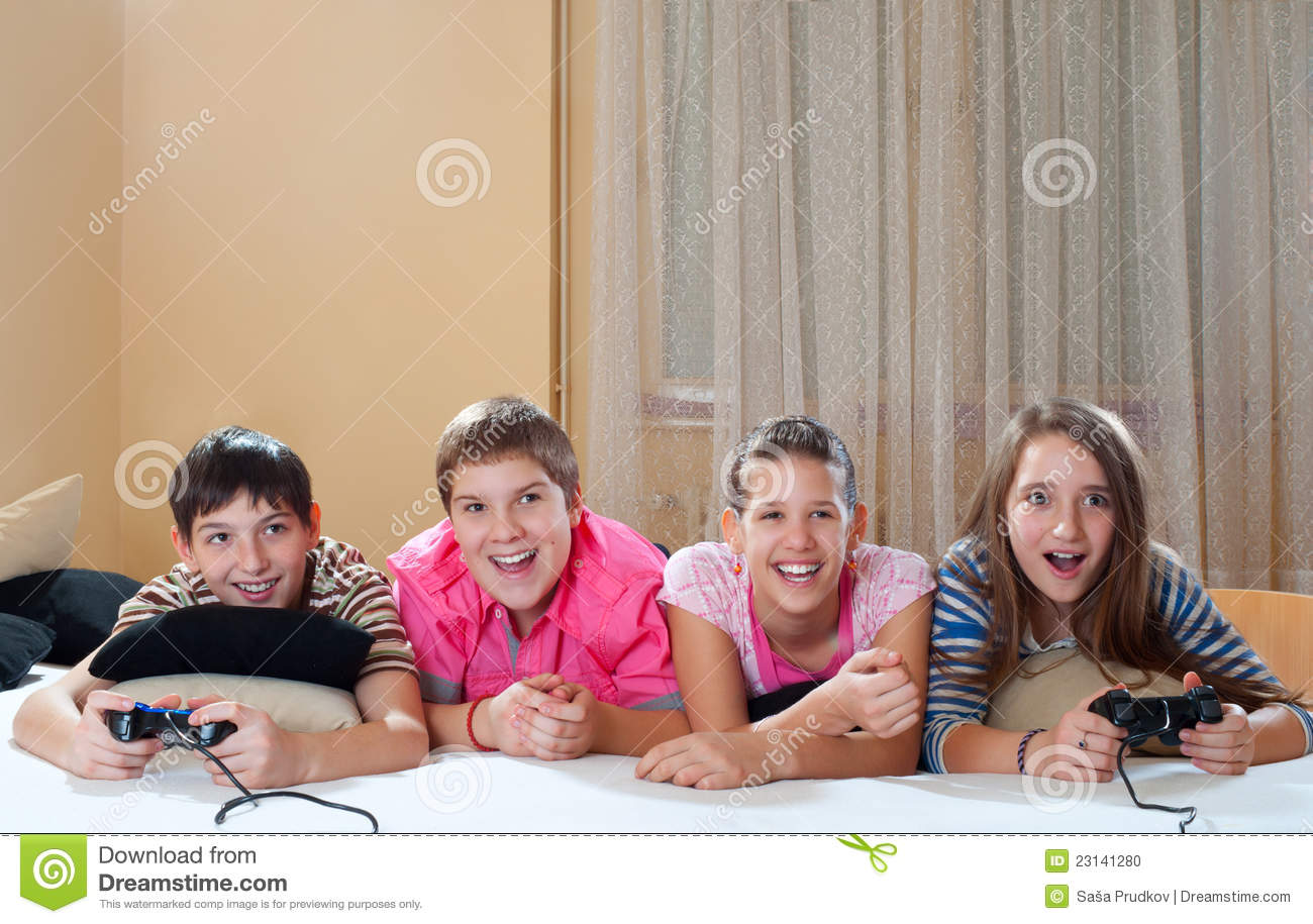 Teenage boys and girls play computer games