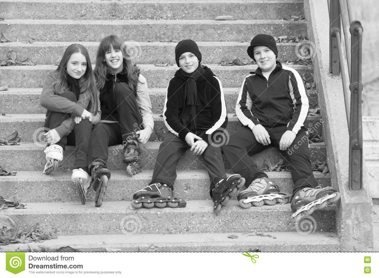 Teenage boys and girls in roller skates sitting on stairs