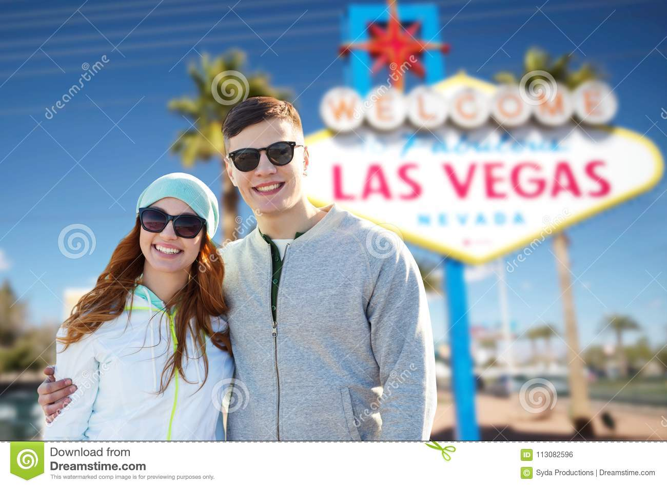 Summer holidays, vacation, tourism and travel concept - happy teenage  couple in shades over welcome to fabulous las vegas sign background