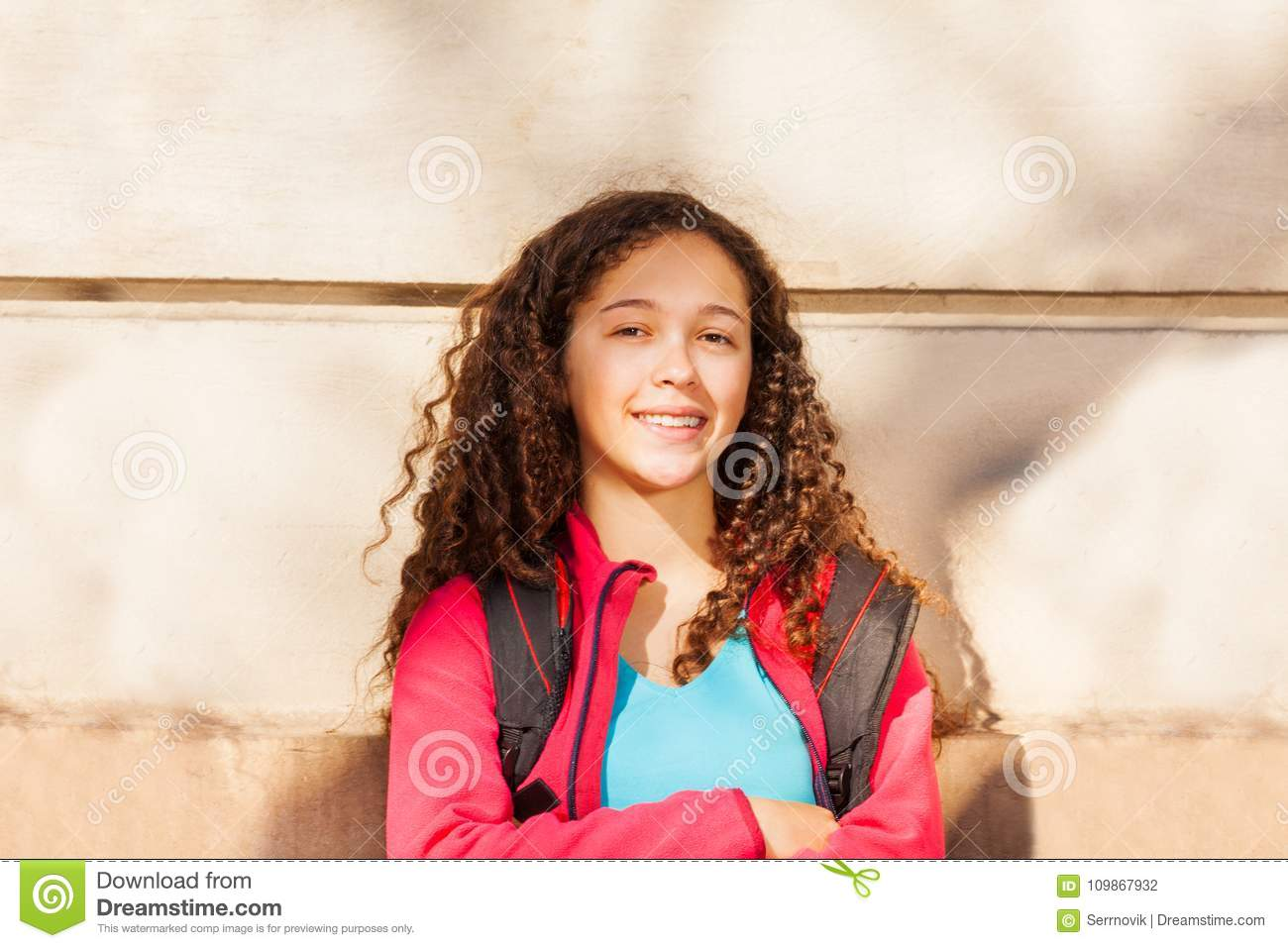 5b5e19f929c Close-up portrait of teenage curly-haired girl with backpack, standing  against the wall at sunny day and looking at camera