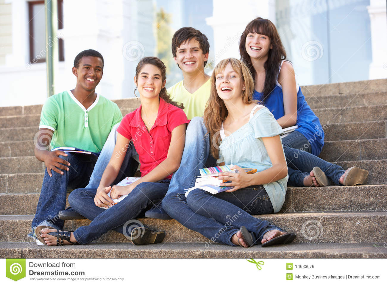Teenage Friends Sitting On College Steps Outside Royalty