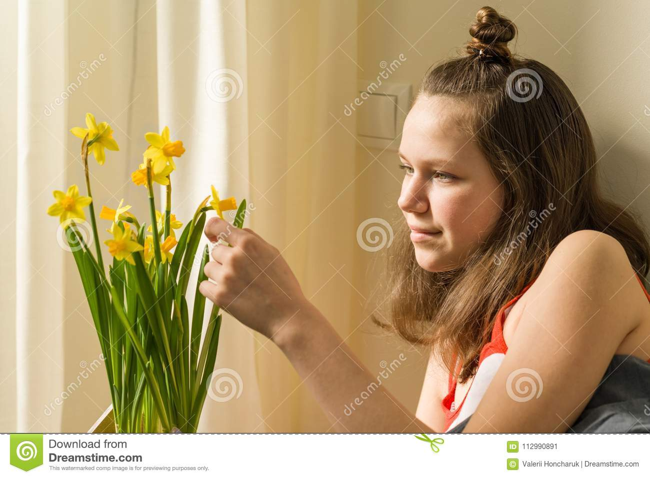 Teenage girl and bouquet of yellow spring flowers