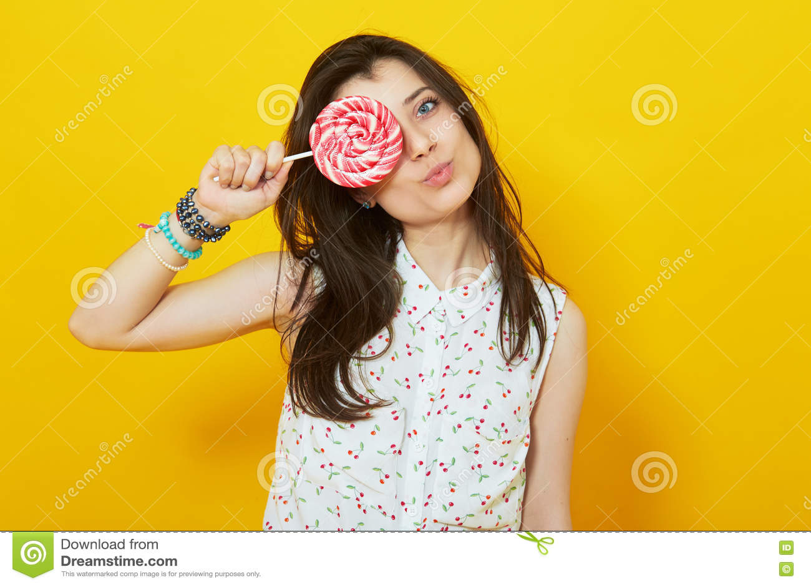 Teenage girl on bright vivid yellow background holding lollipop