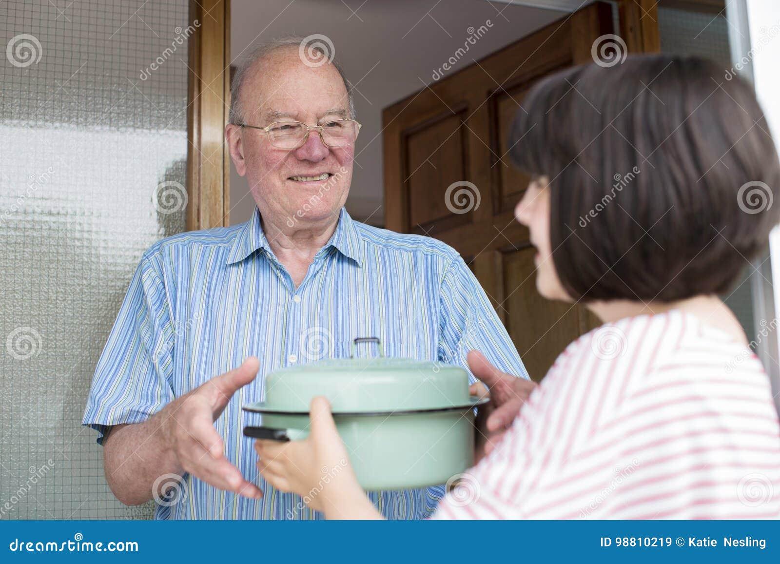 Teenage Girl Bringing Meal For Elderly Male Neighbour