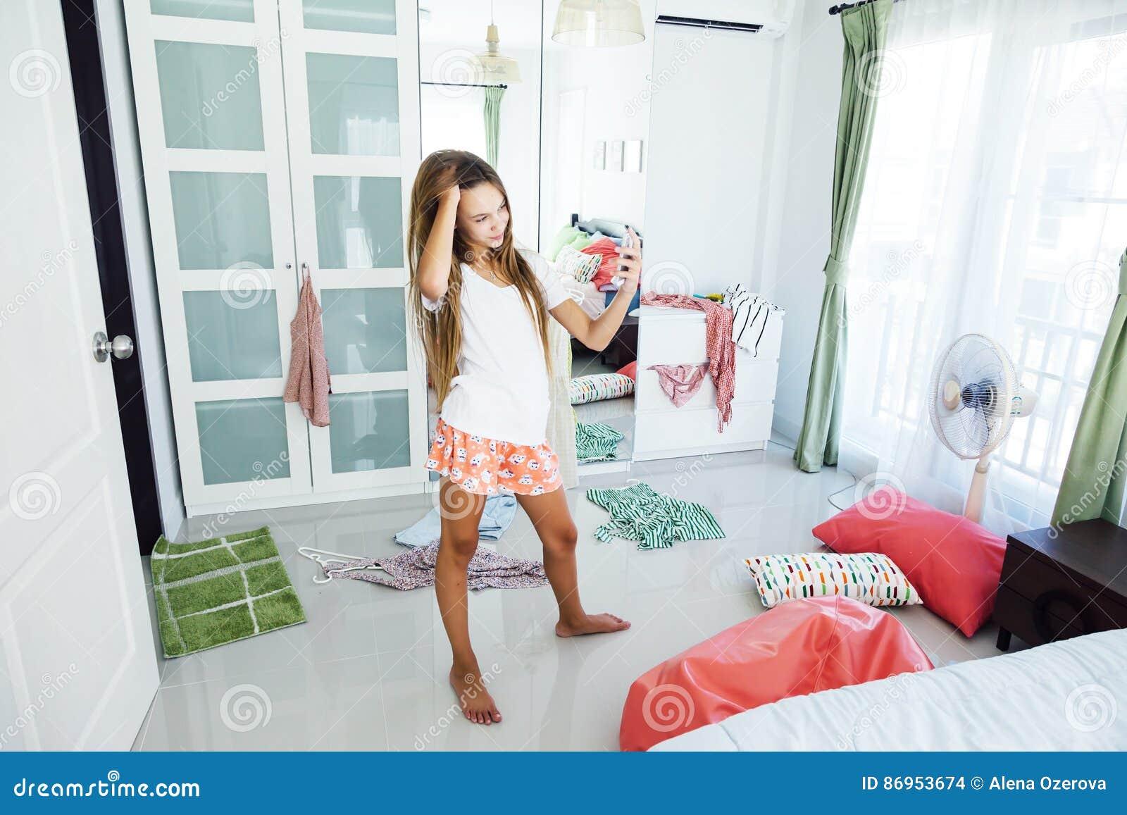 Teenage girl choosing clothing in closet